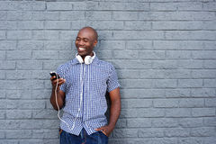 有耳机和手机的愉快的非洲年轻人 免版税库存照片