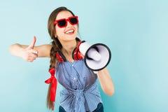 有耳机和扩音器的年轻性感的妇女 免版税库存图片