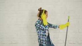 有耳机和拖把的一个少妇准备好家庭清洁 跳舞和唱歌对好音乐 股票视频