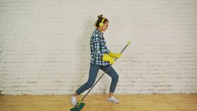有耳机和拖把的一个少妇准备好家庭清洁 跳舞和唱歌对好音乐 股票录像