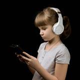 有耳机和电话的女婴在黑暗的背景 免版税库存图片