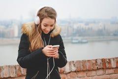 有耳机和电话的愉快的十几岁的女孩喜欢听到音乐并且微笑 免版税图库摄影