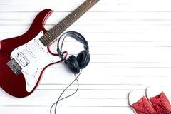 有耳机和红色运动鞋的电吉他在白色木 免版税库存图片