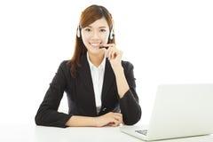 有耳机和膝上型计算机的年轻专业女商人 免版税库存图片