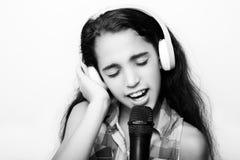 有耳机和话筒的美国黑人的小女孩 库存图片