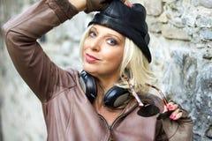 有耳机和黑帽会议的时尚妇女 免版税图库摄影