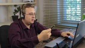 有耳机工作的微笑的英俊的用户支持操作员在电话中心 股票视频