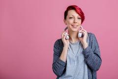 有耳机的一个女孩在她的脖子是微笑 免版税库存照片
