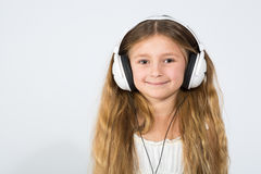 有耳机的一个微笑的女孩 库存照片