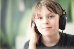 有耳机的一个男孩 库存照片