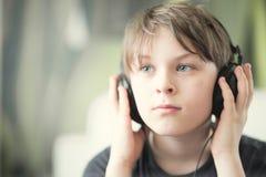 有耳机的一个男孩 库存图片