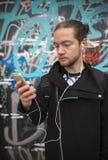 有耳机的一个年轻人在墙壁背景 库存图片