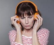 有耳机的不快乐的成熟妇女在她的头 库存照片