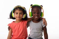 有耳机的两个可爱的小女孩 查出 免版税库存图片