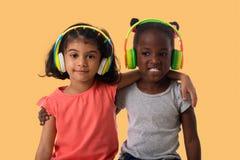 有耳机的两个可爱的小女孩 免版税库存照片