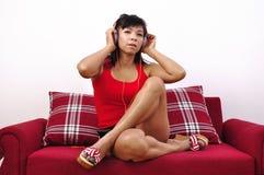 有耳机的亚裔妇女坐红色沙发 库存照片