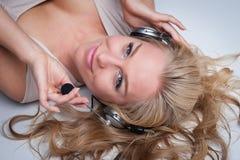 有耳机的俏丽的妇女。 免版税库存图片