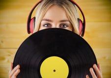 有耳机的反对黄色木盘区的妇女和纪录 免版税库存图片