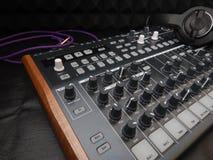 有耳机的合成器在与紫色补丁缆绳的黑皮革背景 库存照片