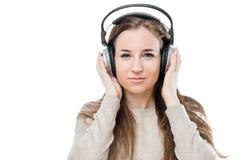 有耳机的听到好音乐的一个女孩的画象 免版税库存照片