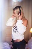 有耳机的听到摇滚乐的美丽的愉快的女孩画象  免版税库存图片