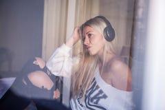 有耳机的听到流行音乐的美丽的女孩画象  免版税图库摄影