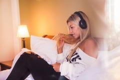 有耳机的听到流行音乐的美丽的愉快的女孩画象  免版税库存照片
