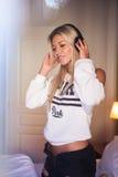 有耳机的听到流行音乐的美丽的愉快的女孩画象  图库摄影