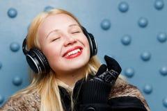 有耳机的听的音乐,特写镜头微笑的姜女孩 免版税库存照片