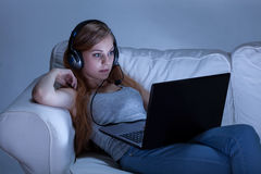 有耳机的女孩使用计算机 免版税库存照片