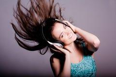 有耳机的女孩唱歌在白色背景的 库存照片