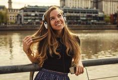 有耳机的女孩在城市 库存图片