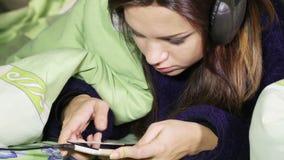 有耳机的女孩在床上 股票视频