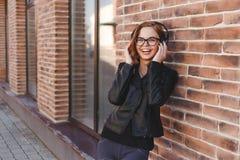 有耳机的女孩在灰色背景 免版税库存照片