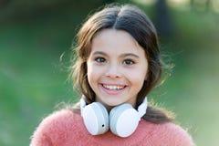 有耳机的女孩逗人喜爱的孩子 原因您应该使用耳机 耳机改造了世界 耳机带来保密性 库存图片