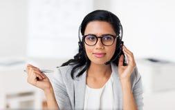 有耳机的女实业家谈话在办公室 库存图片