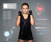 有耳机的妇女听到在健身房的音乐的 库存图片