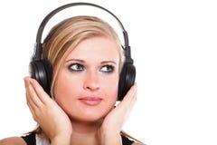 有耳机的妇女听到音乐的查出 免版税库存照片