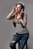 有耳机的妇女听到音乐的 库存照片