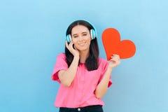 有耳机的妇女听恋爱歌曲的 免版税图库摄影