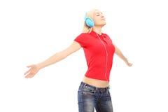 有耳机的妇女听音乐和享用的 免版税库存图片