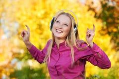 有耳机的妇女在户外秋天 免版税库存图片