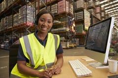 有耳机的妇女在仓库办公室看对照相机 免版税库存图片