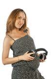 有耳机的孕妇在她的胃 免版税库存图片