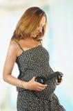 有耳机的孕妇在她的胃 免版税库存照片
