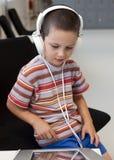 有耳机的孩子 免版税库存照片