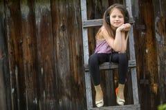 有耳机的小淘气女孩坐一个木活梯在村庄 免版税图库摄影