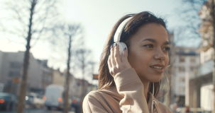 有耳机的少妇享受时间的在城市