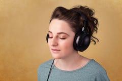 有耳机的少妇听到与拷贝空间的音乐的 免版税库存图片