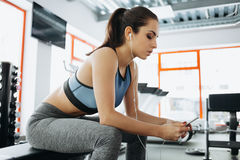 有耳机的少妇听到音乐的在健身房的坚硬锻炼以后 免版税图库摄影